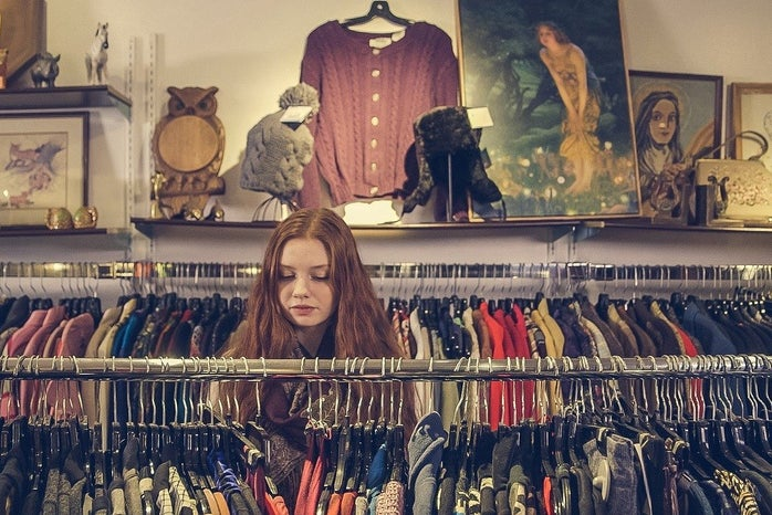 Young woman looking at different racks of clothes at a store.
