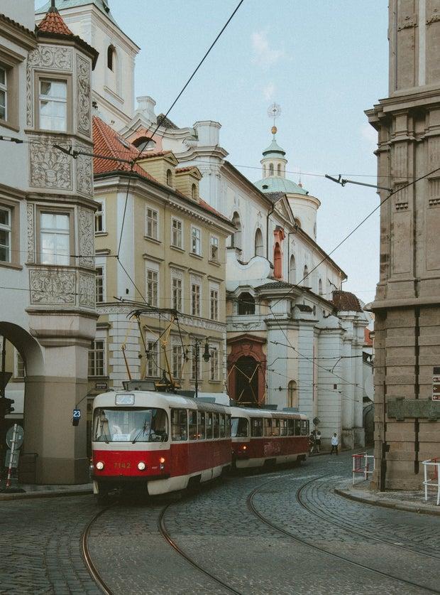 Red Tram Passing Between Concrete Buildings