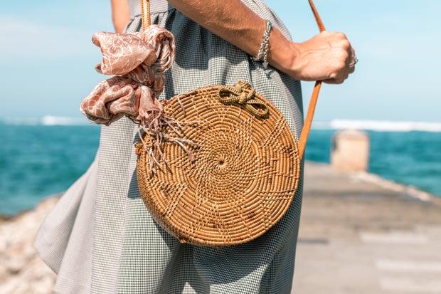 Woman Wearing Grey Skirt And Round Brown Rattan Crossbody