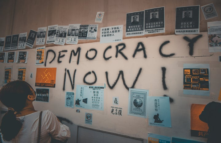 person looking at wall with democracy now! text