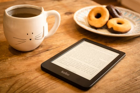 Reading on a tablet with a mug of tea and a plate of donuts