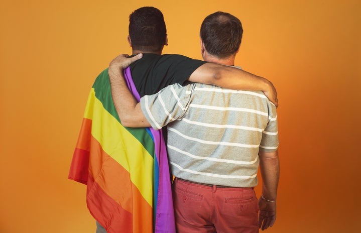 One man with Pride flag, other man hugging him