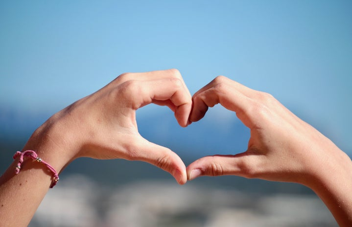 person doing heart hand sign