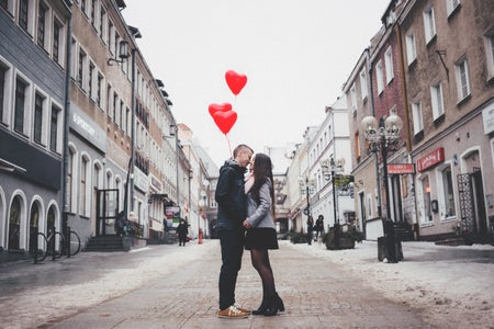 man and woman balloons kissing
