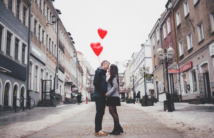 man and woman balloons kissing