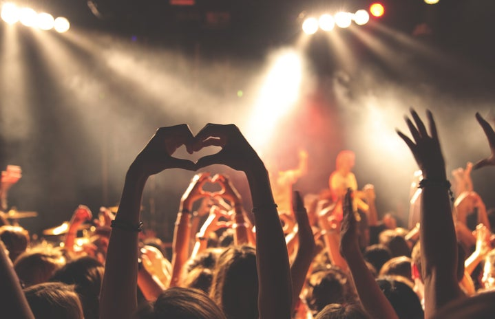 woman at a concert putting hands in a heart shape