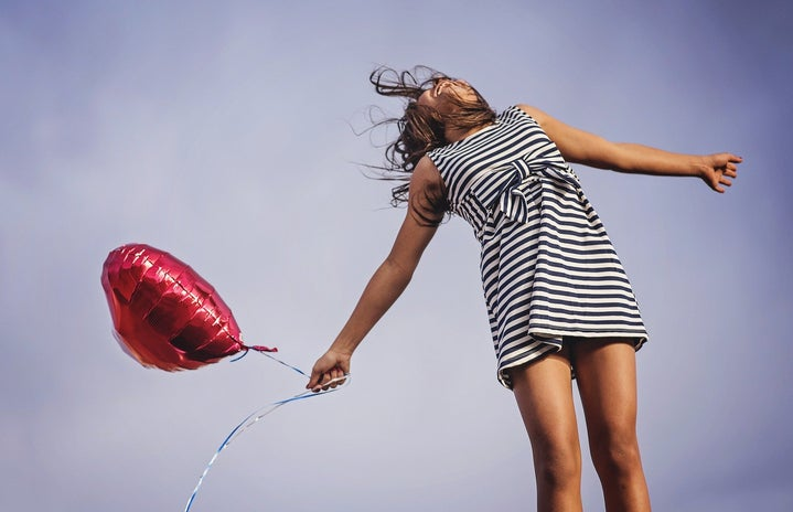 Girl jumping with red heart balloon