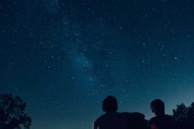 Two people looking at the sky on a starry night