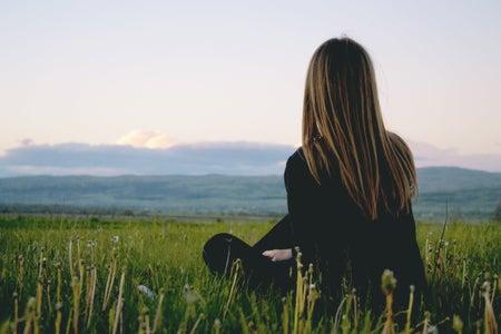 Woman wearing black long sleeved shirt sitting in green grass field near mountains under cloudy sky