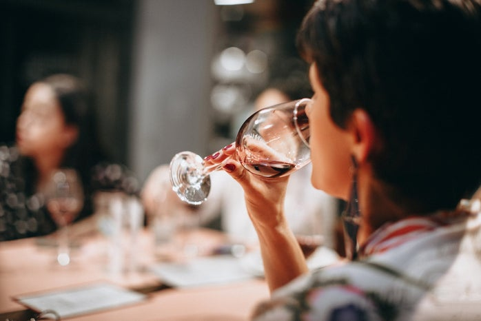 woman drinking out of a wine glass