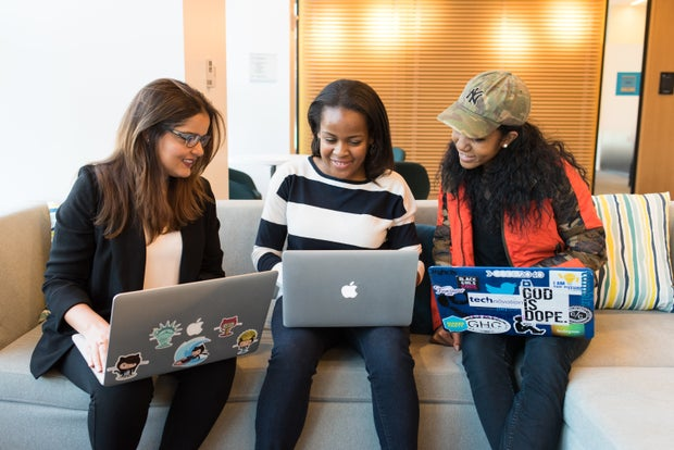 three women sitting on a couch with laptops