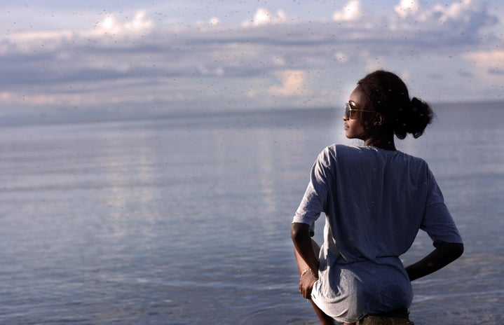 profile of black woman in long sleeve shirt with ocean backdrop