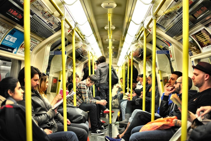 group of people sitting on a crowded train