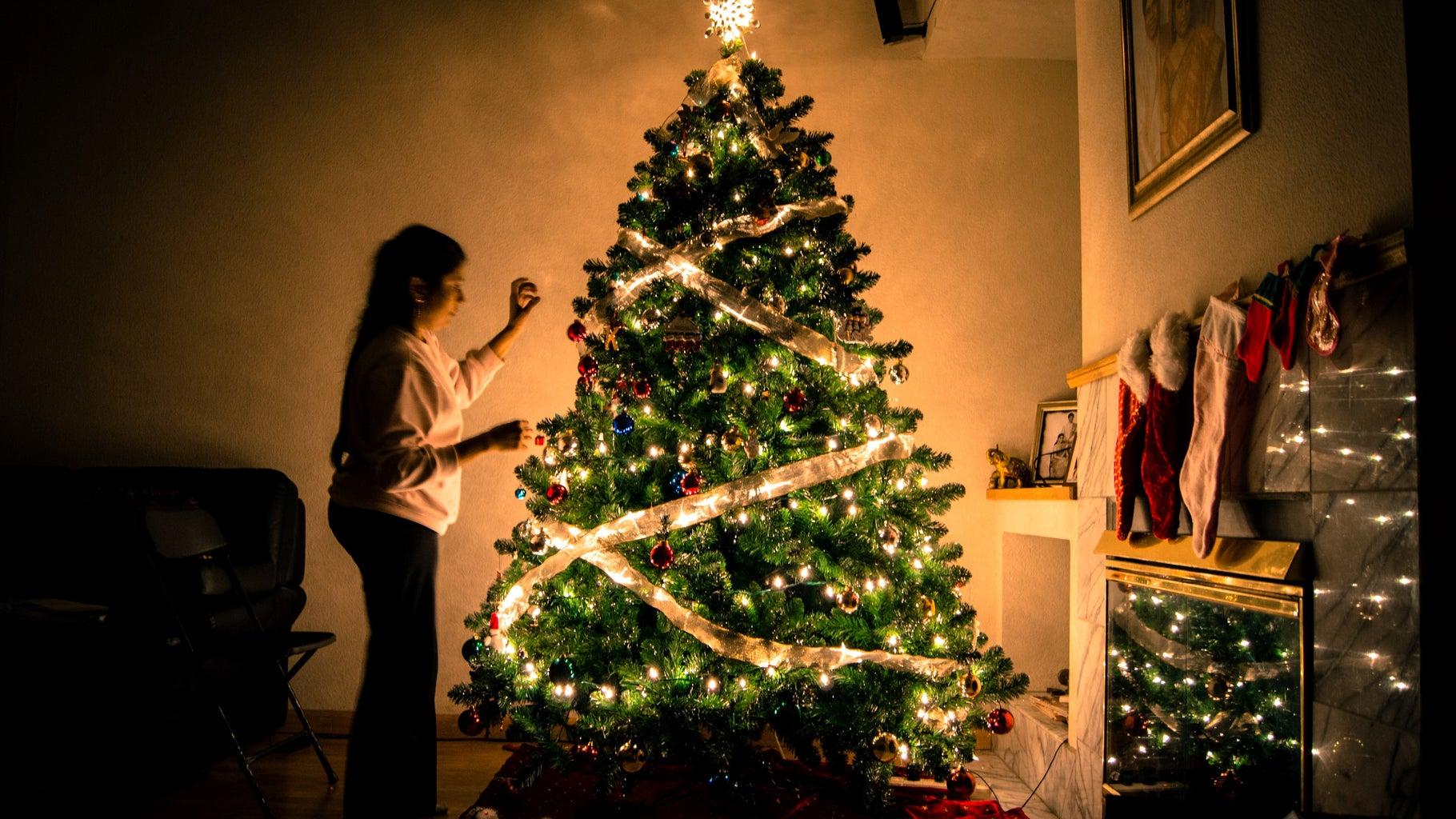 person decorating christmas tree at night