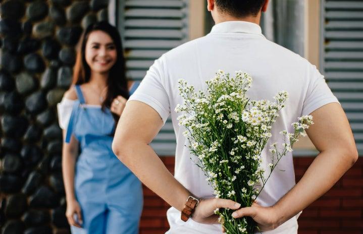 Boy hiding flowers for girl