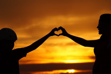Two people holding hands in heart shape during sunset
