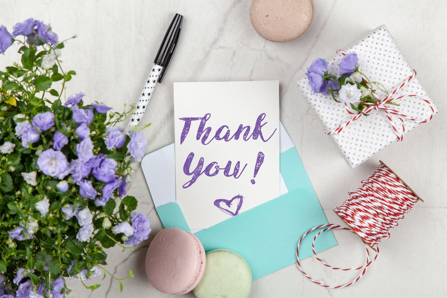 thank you note with pen, gift, cookies, and flowers