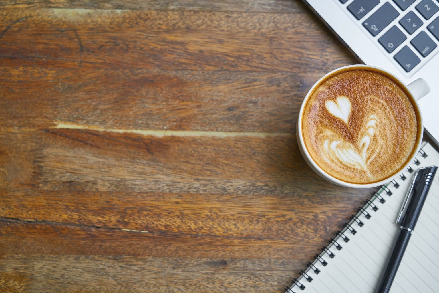 wooden background with laptop and coffee