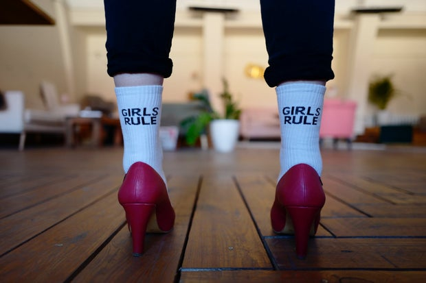 woman wearing red high heels with white socks that say girls rule
