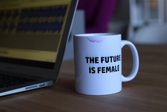 Laptop with white mug that says the future is female with a lipstick mark