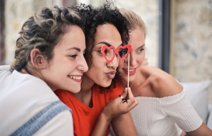 3 women posing for photo together, one with heart glasses