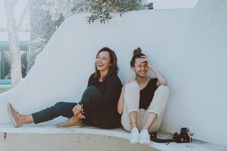 2 women sitting on white bench