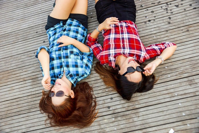 2 women laying on a deck in flannel