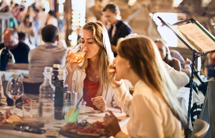 women eating and drinking wine in a restaurant