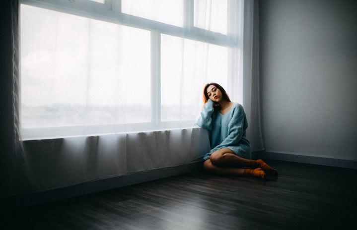 sad girl in blue sweater near window
