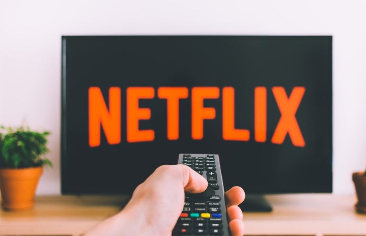 Person holding a remote with a Netflix screen background