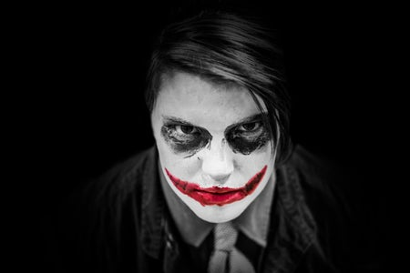 A black and white image of a boy dressed up as the Joker.