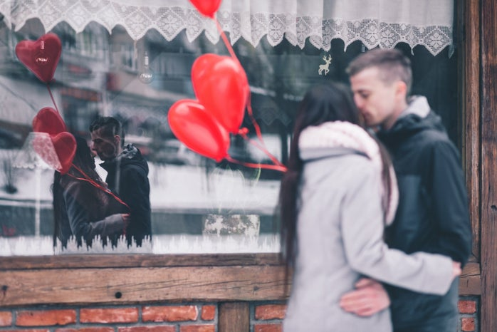 couple kissing outside a window holding red heart balloons