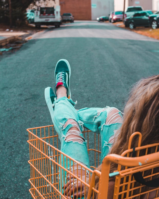 Girl sitting in a shopping cart.