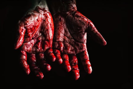 "A woman's hands palm-up covered in ""blood"""
