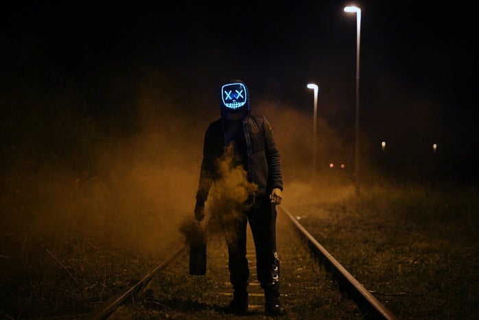 Figure stands on railway in a blue horror movie mask holding a smoking canister.