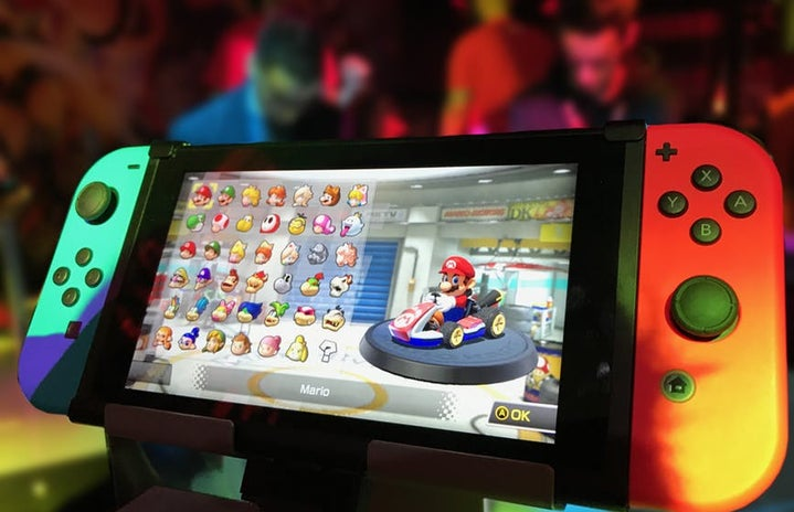 A nintendo switch displaying mario kart is on a display case in front of  blurry convention scene in the background