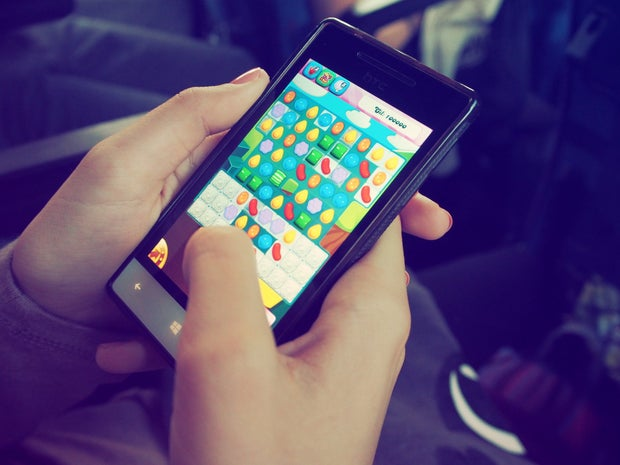 A smartphone user holds their phone, playing a game that looks like Candy Crush