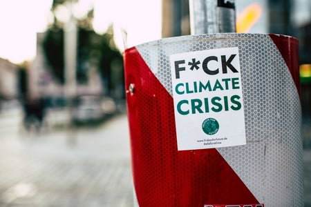 """A white and red trash can/bin has a sticker on it that says """"F*CK Climate Crisis"""""""