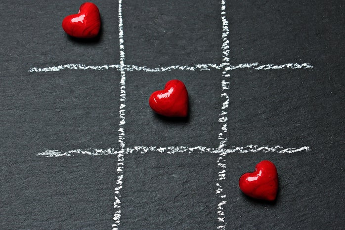 Three red candy hearts stand out against a grey background in a game of tic-tac-toe