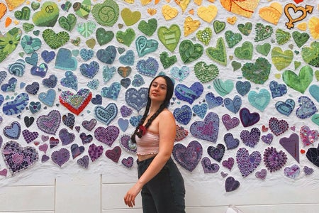a picture of me in front of a wall of rainbow hearts