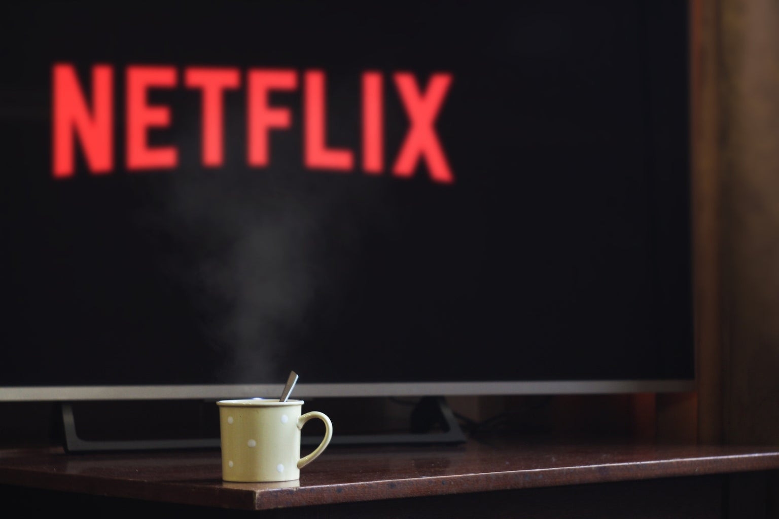 """A fuzzy screen in the back ground might say """"netflix"""" but the image's selective focus is on a mug of some sort."""