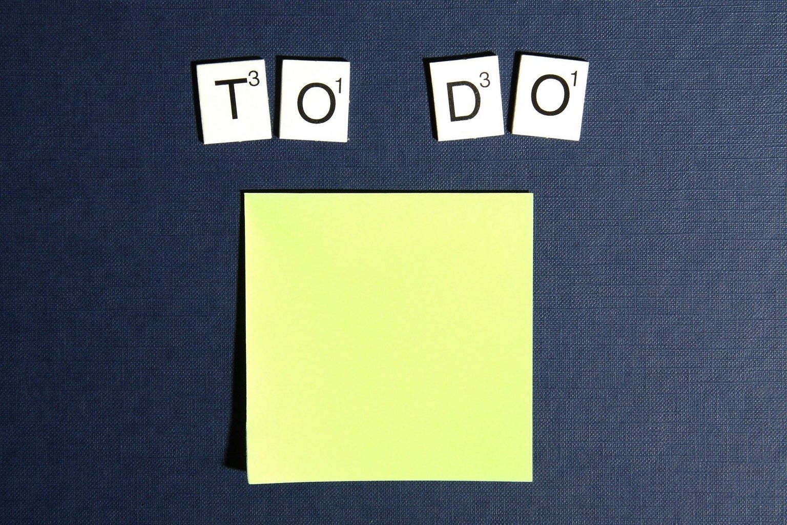 """Scrabble tiles spell out """"To Do"""" on a blue background above a yellow sticky note"""