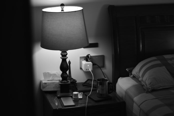 black and white nightstand with lamp, tissues, mug, and charger