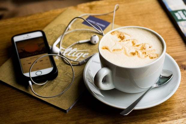 phone, headphones, and coffee with foam art