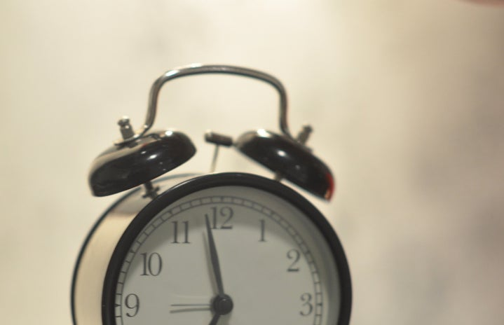 white and black alarm clock with hand on gray table