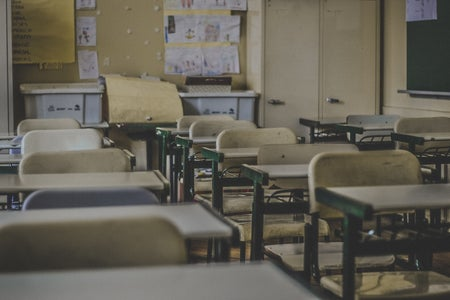 empty classroom with wooden chairs and desks