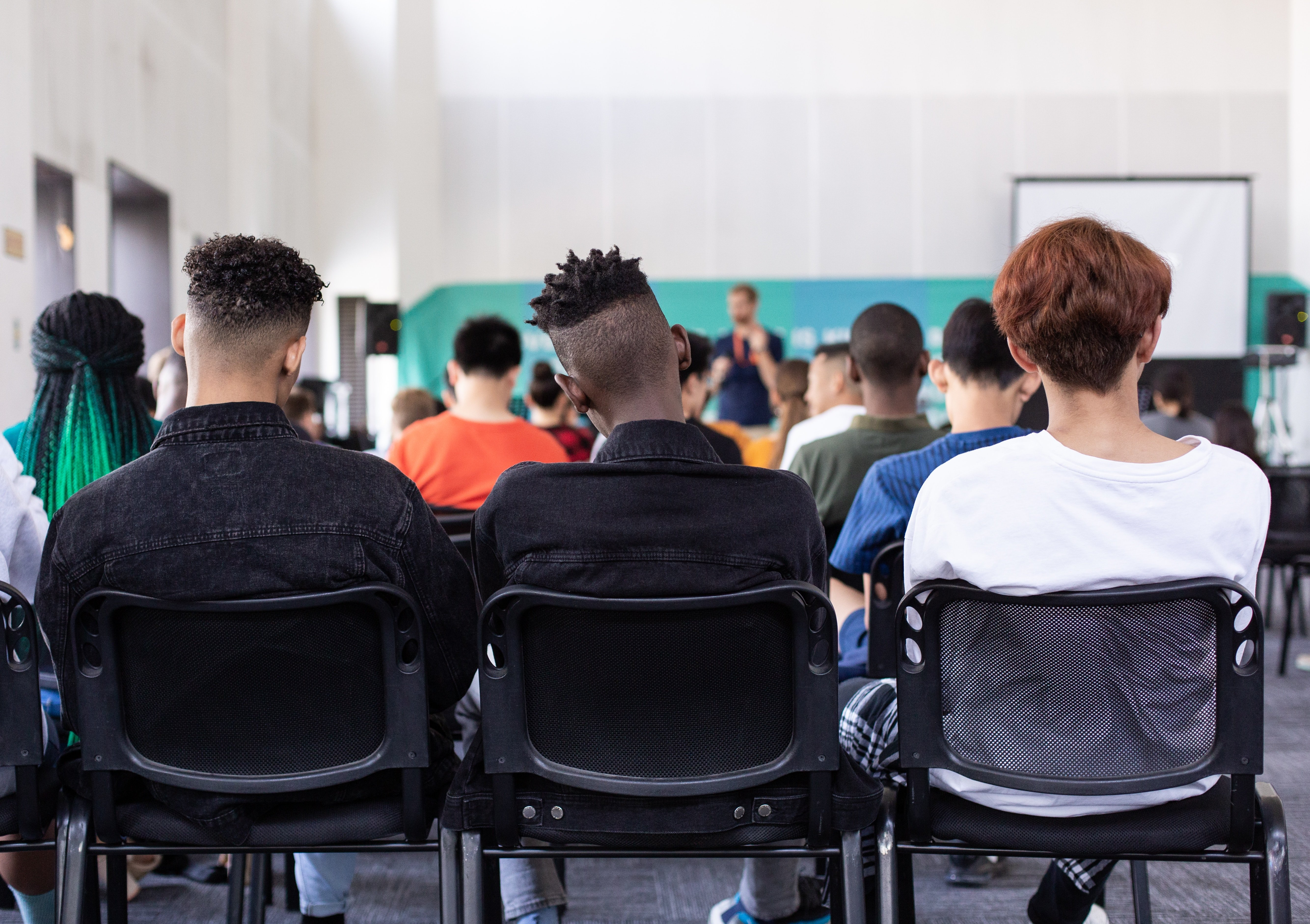 people sitting in chairs in a classroom viewed from behind