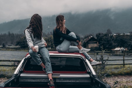 Two girls sitting on sitting on the hood of a car