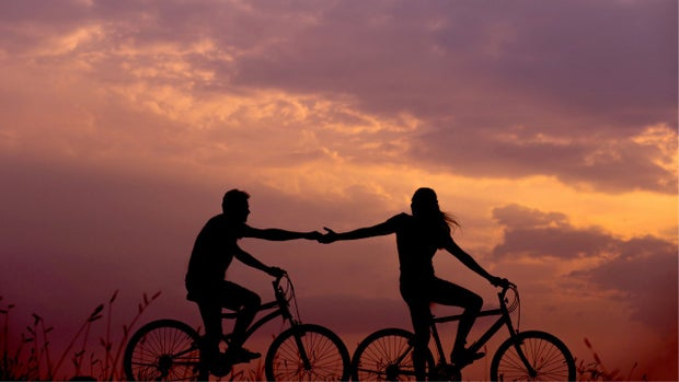 man and woman on bikes at sunset