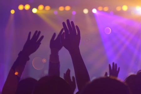 people with their hands raised during a concert